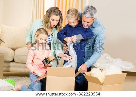 Portrait of happy family opening boxes in living room - stock photo
