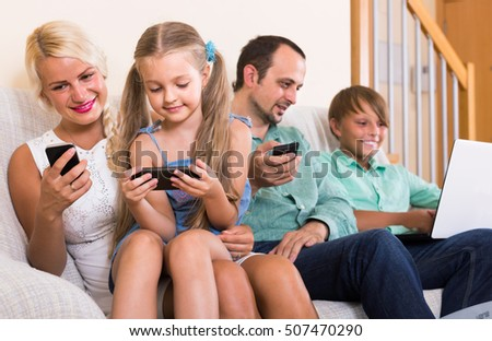 Portrait of happy family playing with gadgets at home