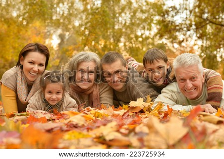 Portrait of happy  family relaxing in autumn forest - stock photo
