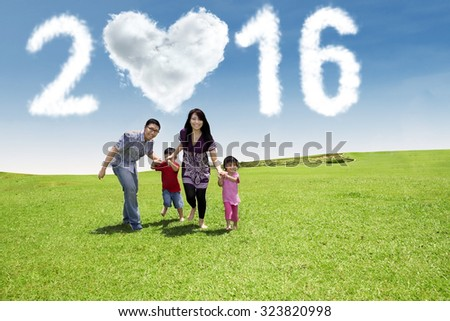 Portrait of happy family running together on the meadow while holding hands under cloud shaped numbers 2016