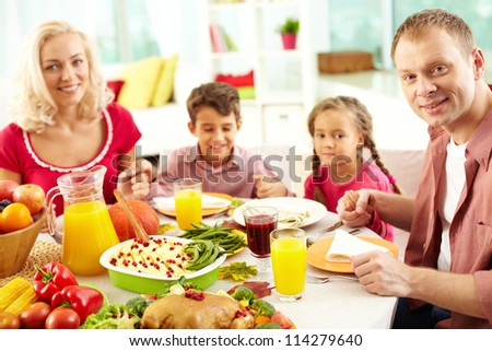Portrait of happy family sitting at festive table and looking at camera while holding each other by hands - stock photo