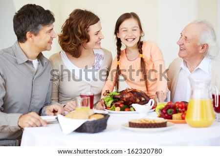 Portrait of happy family sitting at festive table and looking at joyful girl during Thanksgiving dinner - stock photo