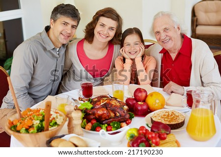 Portrait of happy family sitting at festive table on Thanksgiving day - stock photo