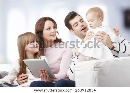 Portrait of happy family sitting at sofa at living room while having fun. - stock photo