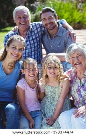 Portrait of happy family sitting in back yard - stock photo