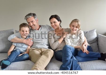 Portrait of happy family sitting in sofa