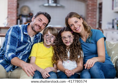 Portrait of happy family sitting on a sofa at home - stock photo
