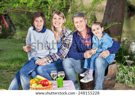 Portrait of happy family sitting on chairs at campsite