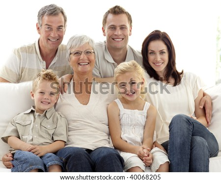 Portrait of happy family sitting on sofa - stock photo