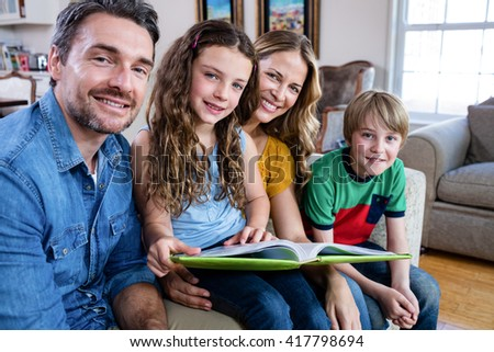 Portrait of happy family sitting on sofa with photo album at home