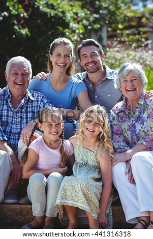Portrait of happy family sitting on steps in back yard - stock photo