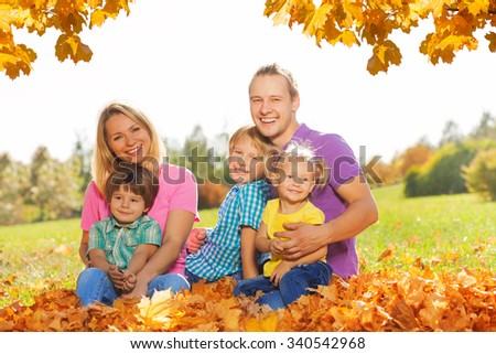 Portrait of happy family sitting on the leaves - stock photo