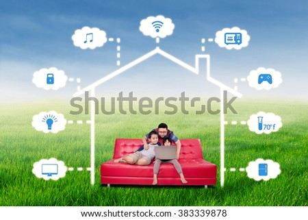 Portrait of happy family sitting on the sofa while using laptop to control a smart house technology system, shot outdoors - stock photo