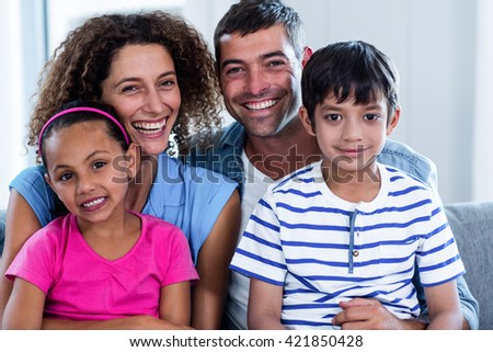 Portrait of happy family sitting together on sofa in living room