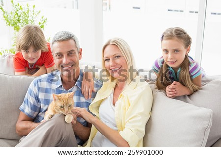 Portrait of happy family sitting with cat on sofa at home