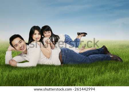 Portrait of happy family smiling at the camera while relaxing and lying on the grass at field - stock photo