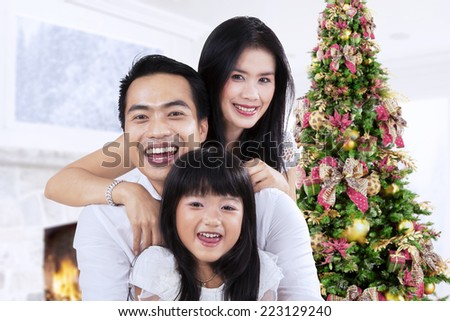 Portrait of happy family smiling on camera at home in christmas day  - stock photo