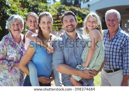 Portrait of happy family standing in back yard during sunny day - stock photo