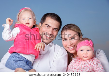 Portrait of happy family standing on blue clear sky background, parents with two adorable daughters having fun outdoors - stock photo