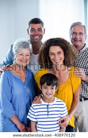 Portrait of happy family standing together at home - stock photo