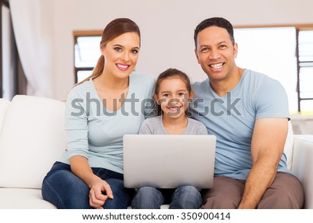 portrait of happy family using laptop computer at home - stock photo