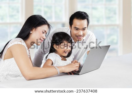 Portrait of happy family using laptop computer together at thome while smiling happy - stock photo