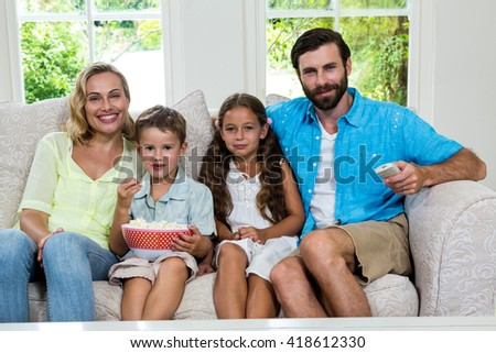 Portrait of happy family watching tv while sitting on sofa at home