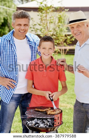 Portrait of happy family with barbecue outdoors - stock photo