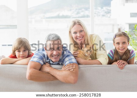 Portrait of happy family with cat on sofa at home