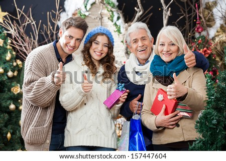 Portrait of happy family with Christmas presents and shopping bags gesturing thumbs up in store - stock photo