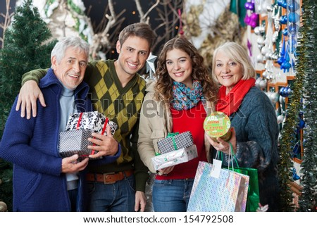 Portrait of happy family with Christmas presents and shopping bags standing together in store