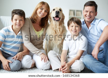 Portrait of happy family with fluffy Labrador having rest at home