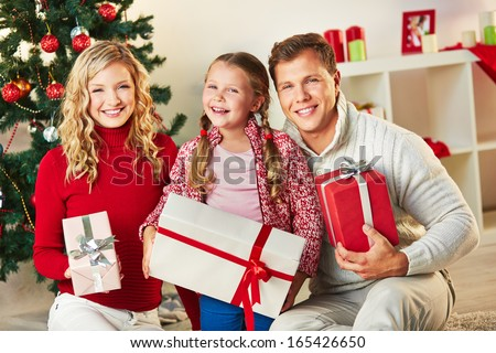 Portrait of happy family with giftboxes looking at camera on Christmas day