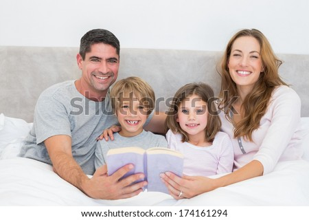 Portrait of happy family with storybook in bed - stock photo