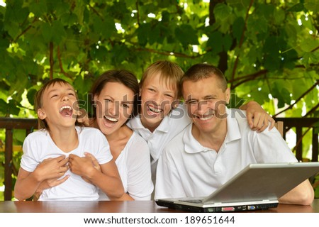 Portrait of happy family with the computer at outside terrace - stock photo