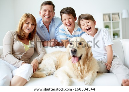 Portrait of happy family with their pet having good time at home - stock photo