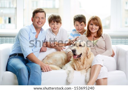 Portrait of happy family with their pet having rest at home
