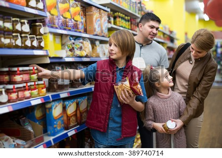 Portrait of happy family with two children in local supermarket
