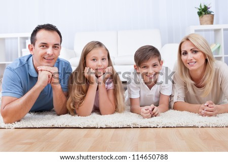 Portrait Of Happy Family With Two Children Laying On Carpet At Home - stock photo