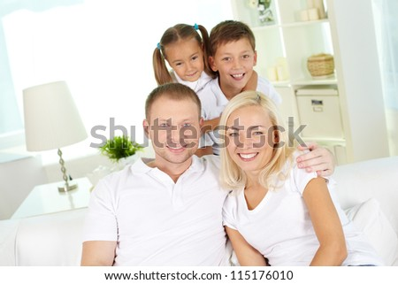 Portrait of happy family with two children looking at camera at home - stock photo