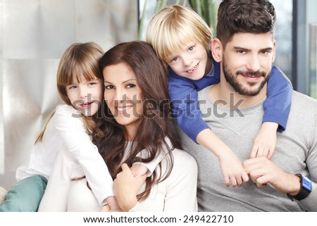 Portrait of happy family with two kids sitting at sofa at living room. - stock photo