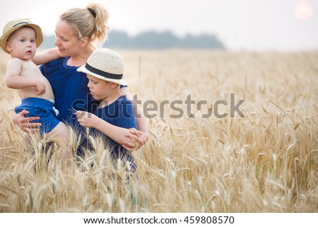 Portrait of happy family: young beautiful mother, adorable toddler boy and cute kid walking in the wheat field and enjoying sunny day. Mom with children. Lifestyle concept - stock photo