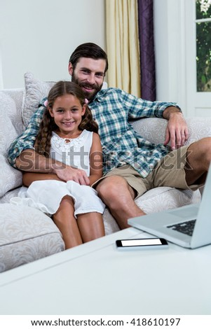 Portrait of happy father and daughter on sofa at home