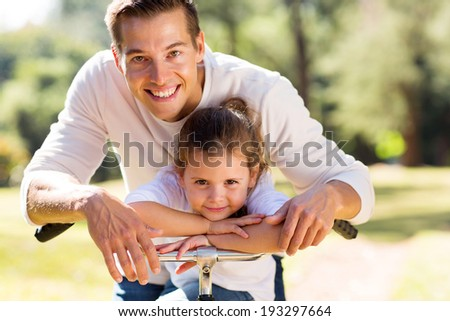 portrait of happy father and his cute daughter outdoors in forest on a bike - stock photo
