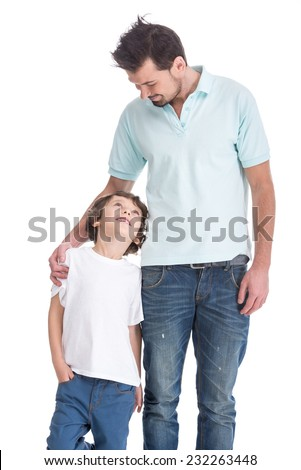 Portrait of happy father and his little son, on the white background. They are looking at each other. - stock photo