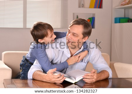 Portrait of happy  father and his son sitting on sofa at home