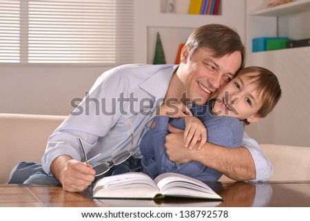 Portrait of happy  father and his son sitting on sofa at home - stock photo