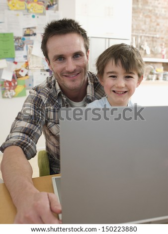 Portrait of happy father and son with laptop sitting at table in house - stock photo