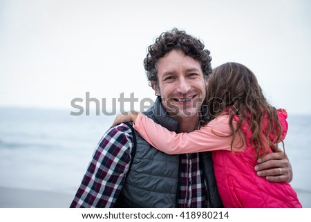 Portrait of happy father carrying daughter at sea shore - stock photo