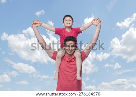 Portrait of happy father carrying son on shoulders against cloudy sky - stock photo
